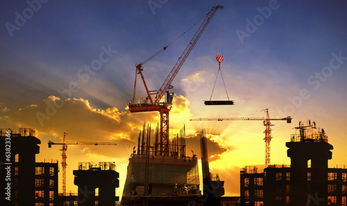 Poster Stad gebouw big crane and building construction against beautiful dusky sky