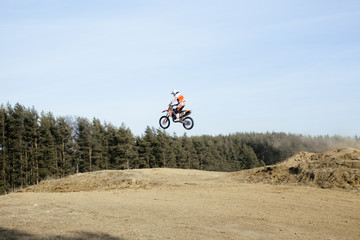 Motorcycle jumping on springboard in forest