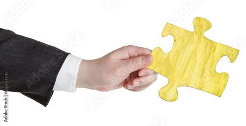 male hand with painted yellow puzzle piece