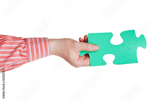 male hand holding big green paper puzzle piece