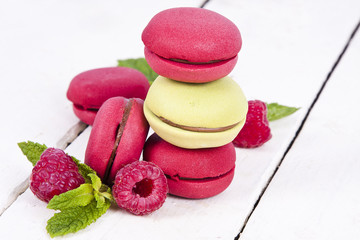 macaroons fresh raspberries on white wooden background