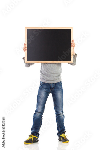 Boy hiding face behind balckboard