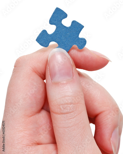 female fingers holding blue puzzle piece