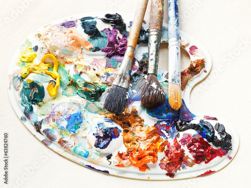 artistic pallette with oils and paint brushes