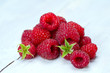 heap of fresh raspberries on wooden surface