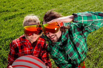 Couple in ski suit and sun glasses have a funny look to the came
