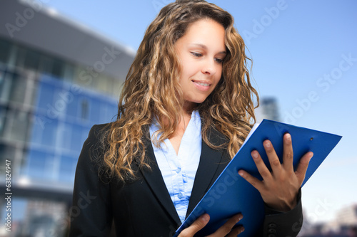 Smiling businesswoman reading some documents