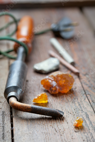 Old soldering iron with rosin and solder on wooden table