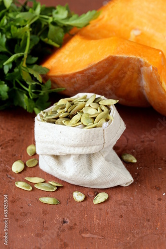 peeled pumpkin seeds and fresh pumpkin on a wooden table
