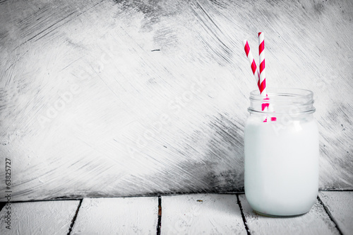 Milk jar on wooden rustic background