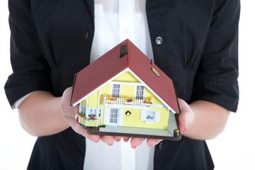 Geschäftsfrau hält Miniatur Haus in den Händen