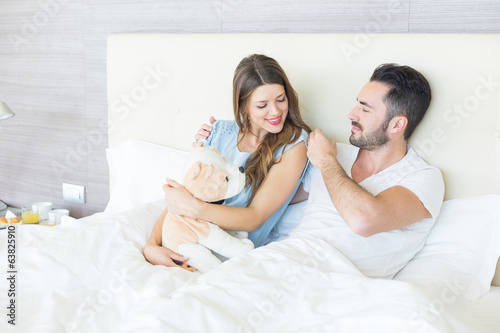 Couple on Bed with Stuffed Animal Toy