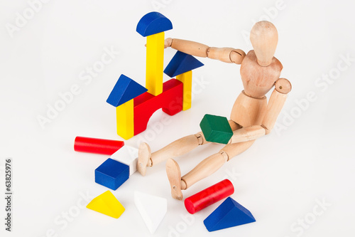 Small wood mannequin sit building colourful blocks isolated on w