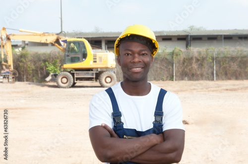 Laughing african worker with crossed arms at construction site