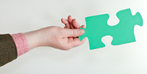 green puzzle piece in male hand