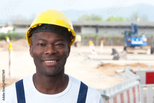 Laughing african worker at construction zone looking at camera