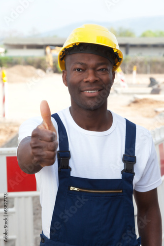African worker at construction zone showing thumb up