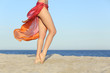 Standing woman legs posing on the beach wearing a pareo