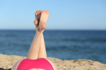Woman legs sunbathing on the beach lying down