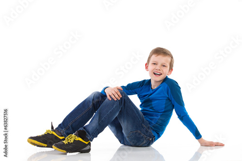 Smiling boy sitting on the floor.