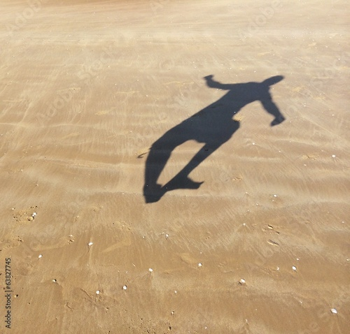 The shadow of a man junping at the beach