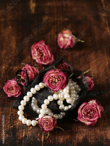 Vintage pearl with dry roses on a wooden background