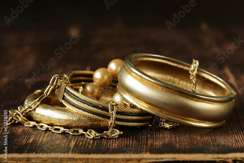 gold and pearl jewelry on vintage wooden background