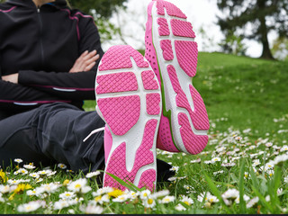 Jogger feet in sport shoes on spring grass