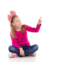 Little girl with hair bow pointing