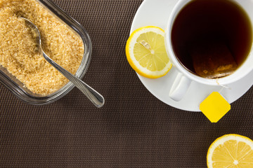 Tea cup, brown sugar and slice of lemon