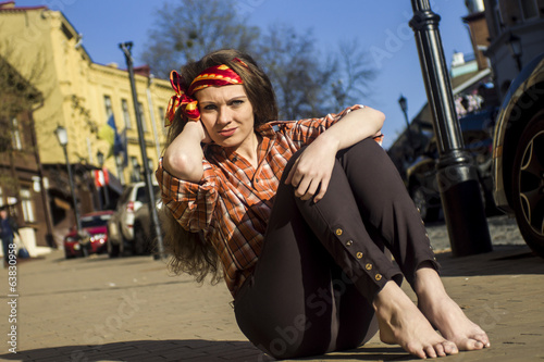 Portrait of a young  woman,   barefoot on a commercial street