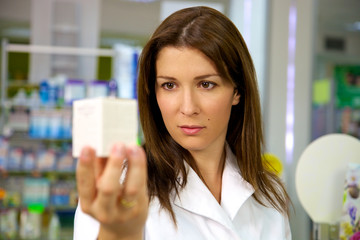 Portrait of doctor holding medicine in pharmacy