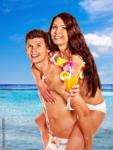 Couple with cocktail at Hawaii wreath beach.
