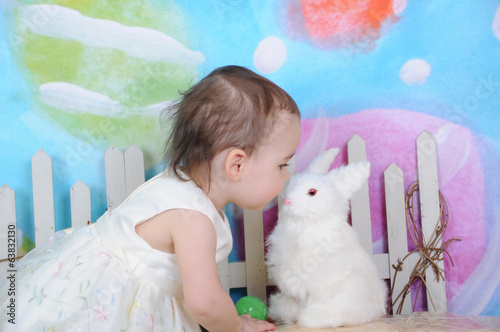 beautiful toddler kissing bunny at easter time