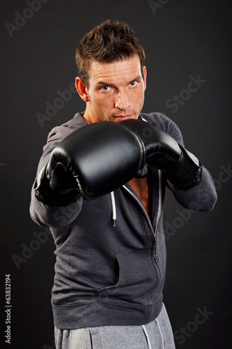 Handsome muscular man boxes with boxer gloves