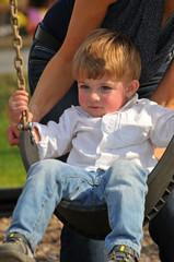 blond little boy swinging on a swing