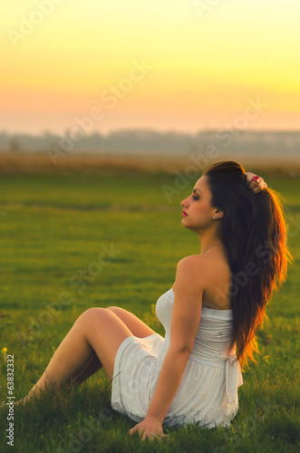Beautiful girl sitting on the meadow at sunset