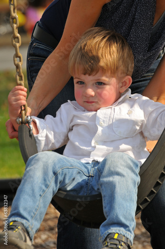 blond little boy swinging on a swing