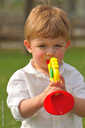 toddler playing with toy trumpet
