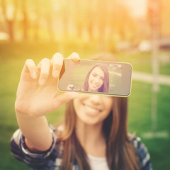 Beautiful young woman photographing herself with phone