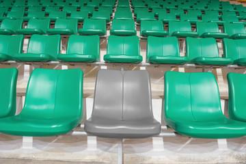 grey stadium seat between green seats
