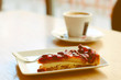 Piece of wild strawberry cake and cup of espresso in cafe
