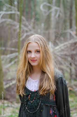 Picture of blonde girl standing in the forest