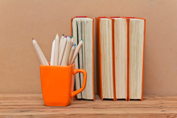 Stack of books and mug with colored pencils