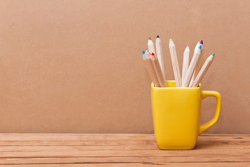 Color pencil in the cup on  wooden background