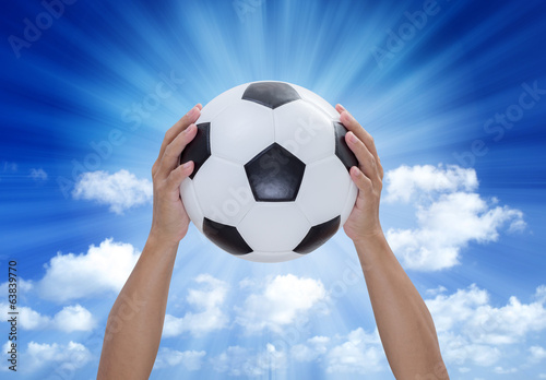 Soccer ball in hands with blue sky and lightray background