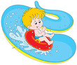 Little boy slides down in a waterpark