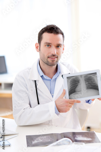 Young doctor showing radiography on a tablet