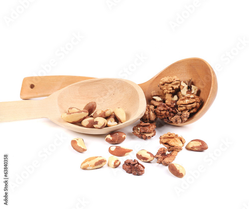 Brazil nuts and walnuts in a wooden spoon.