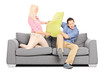 Man and woman having a pillow fight on couch
